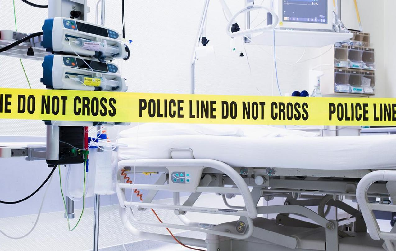 Police tape surrounding a hospital bed